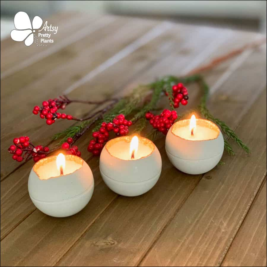3 white, round candles made from cement with berries