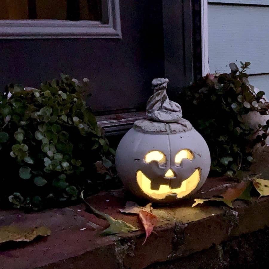 jack o lantern made from concrete with light inside, on a porch step
