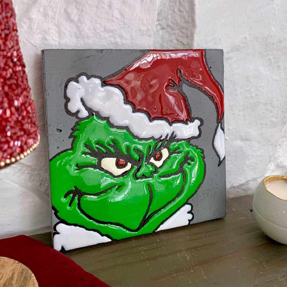 DIY Cement Grinch Decor by fireplace