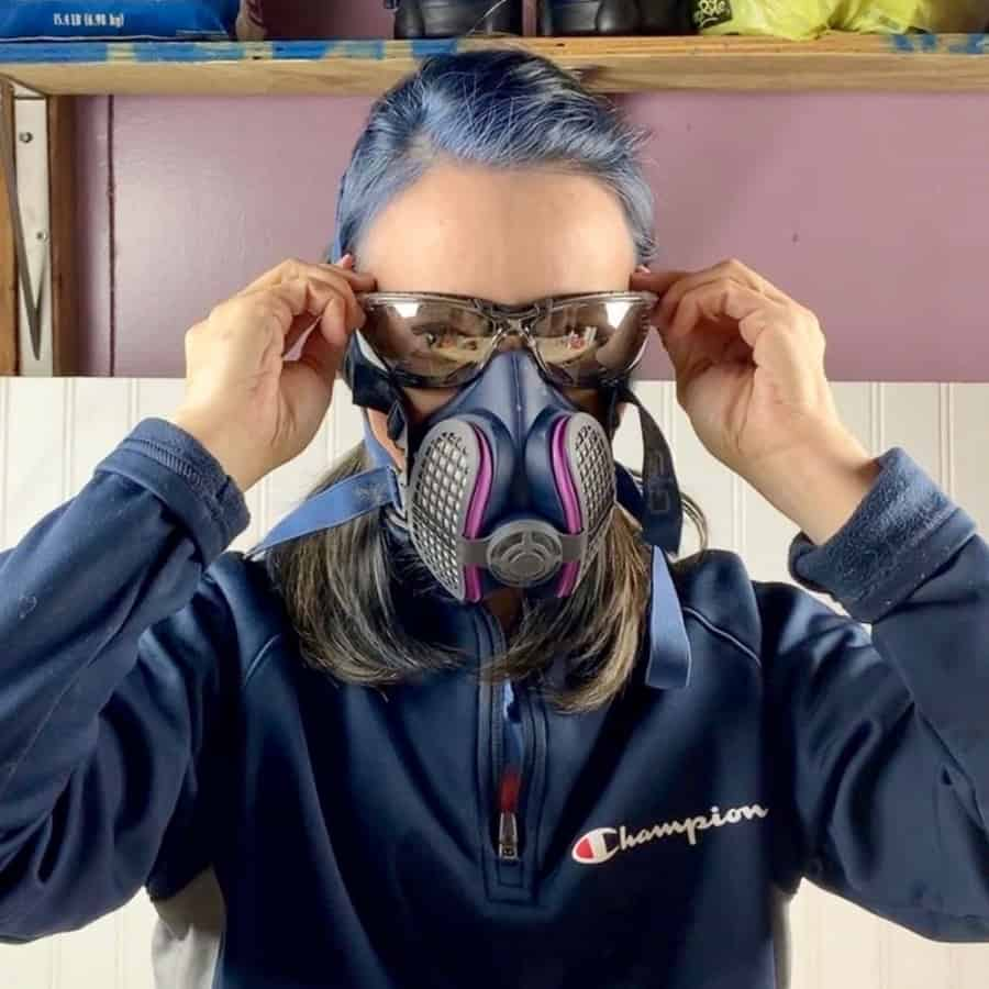 girl with blue hair wearing safety glasses and mask