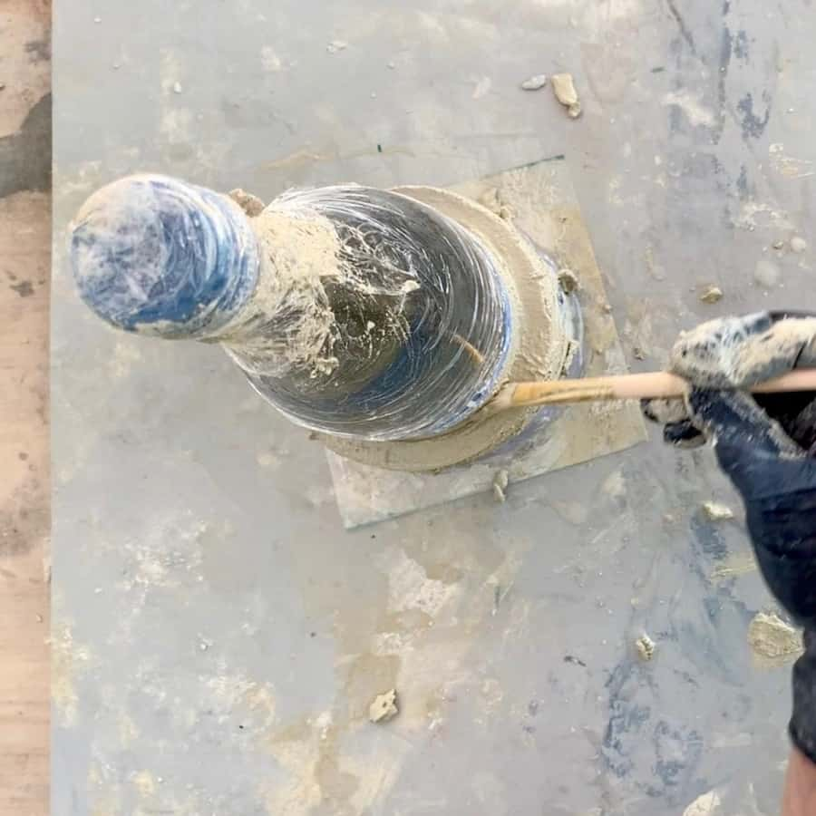 clean up cement on top of collar mold with brush