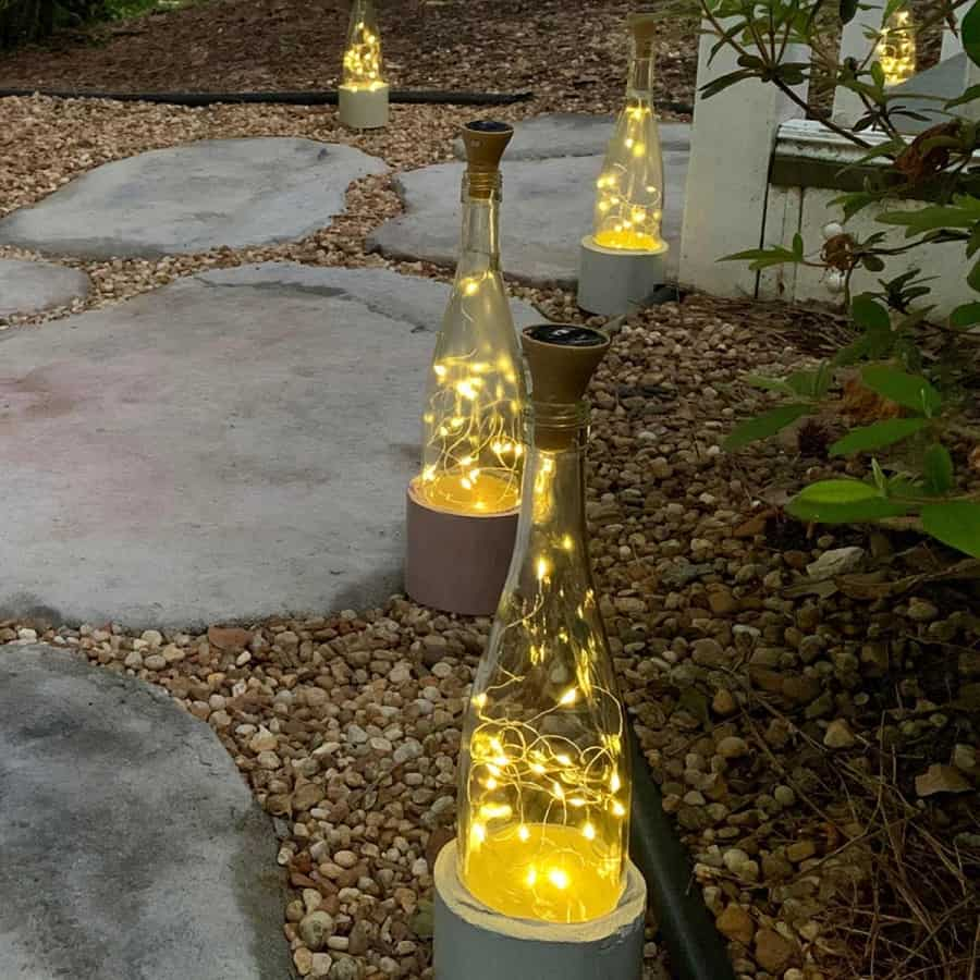 solar fairy lights wine bottle with cement base on stone path