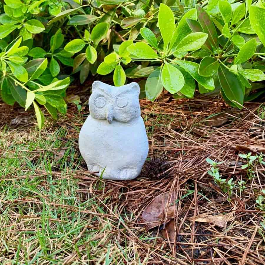 concrete garden owl statue in front of bushes
