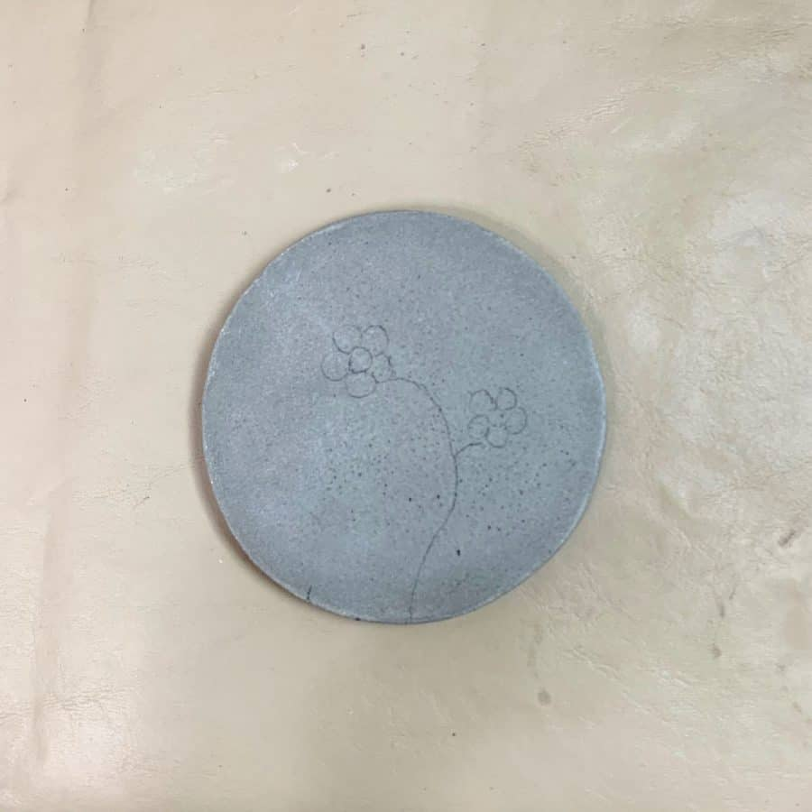 concrete coaster with flower design transferred to it