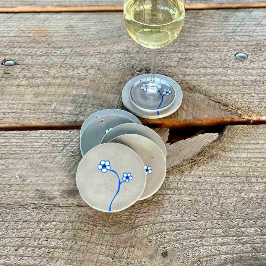 4 diy concrete coasters in pile with wine glass on one