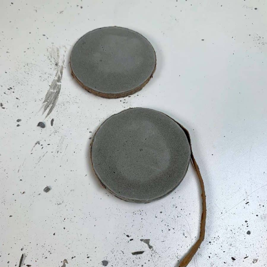 2 diy concrete coasters partially demolded with cardboard peeled back.
