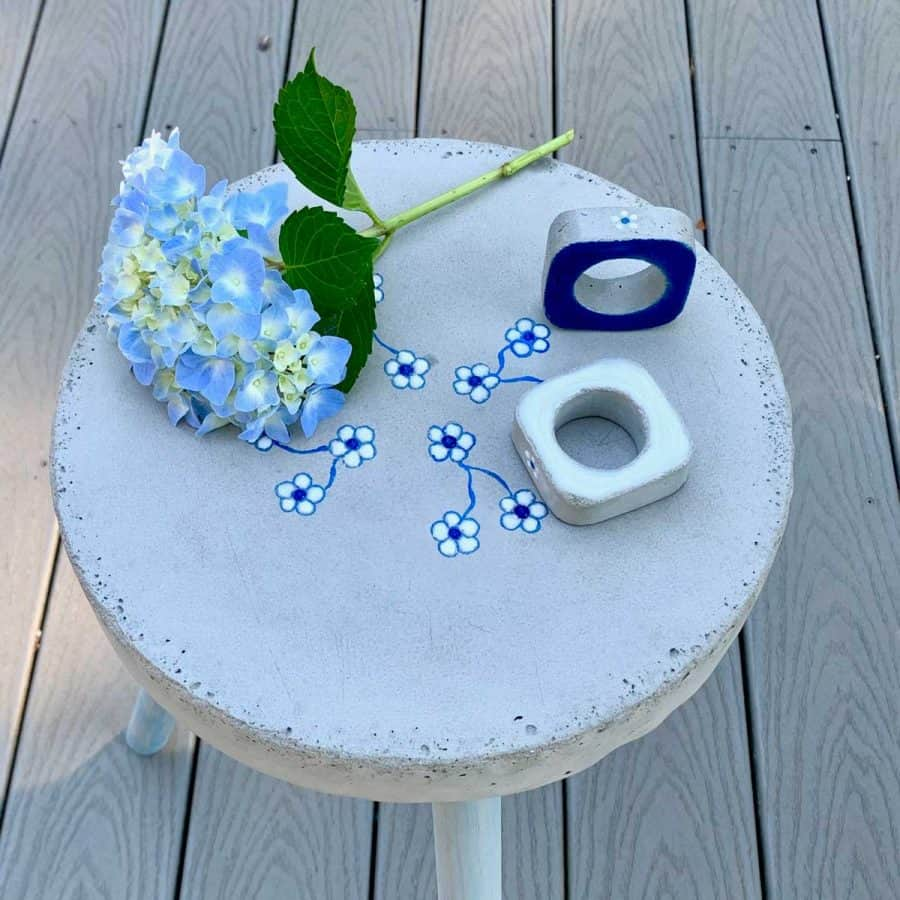concrete napkin rings with bright blue resin on matching concrete side table