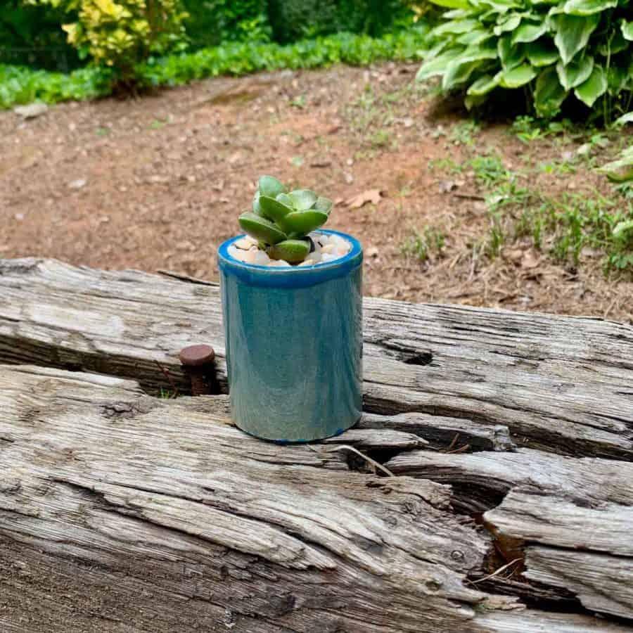 a concrete planter with a blue pottery-like glaze, on a railroad tie