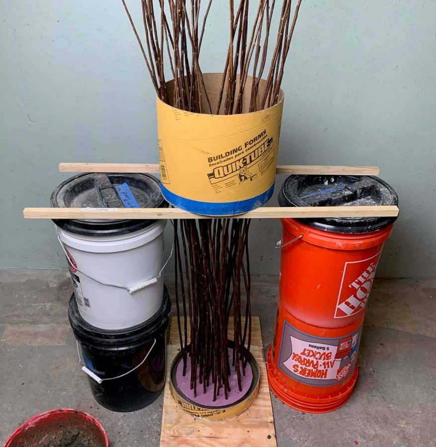 4 buckets supporting the cardboard tube, supporting the diy twig lights stand while inside of cement