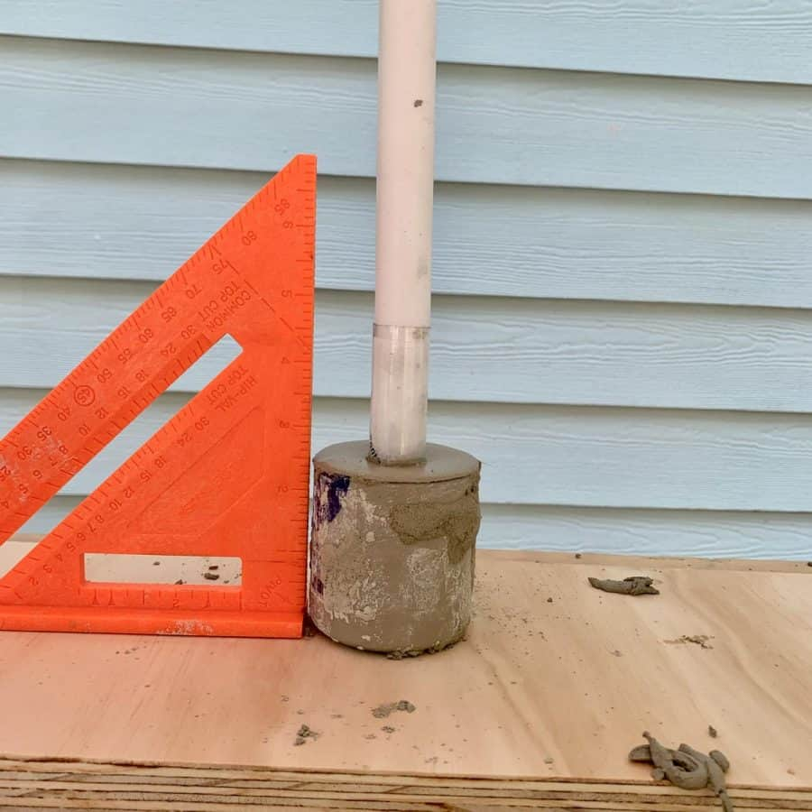 squaring tool showing plumpness of candlestick inside of cement