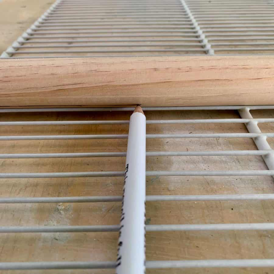 pencil drawing line on wood dowel for legs. Dowel is on wire rack