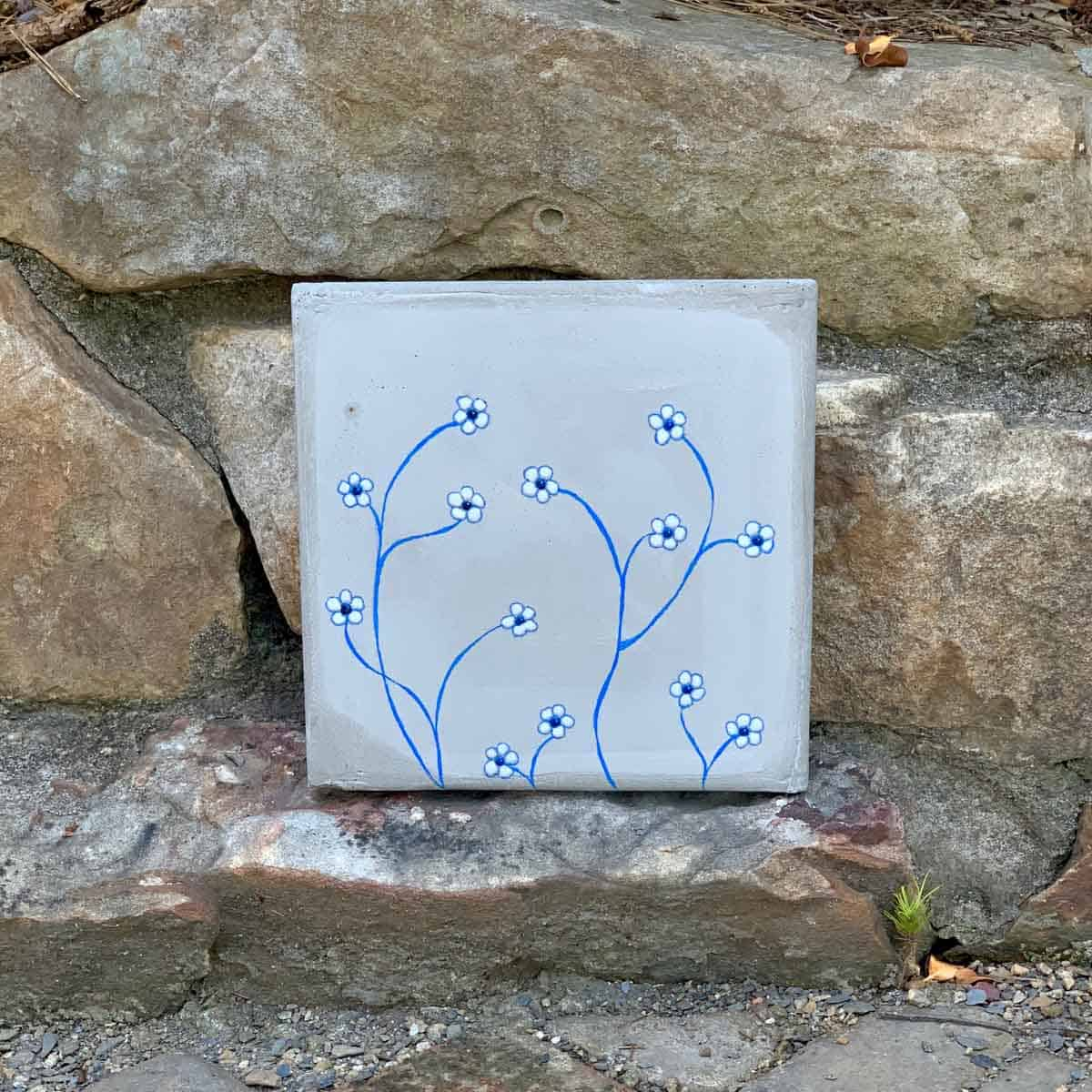 Outdoor DIY Concrete Wall Tile With Flowers against stones