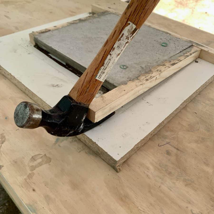 hammer lifting wood sides of outdoor concrete wall tile mold