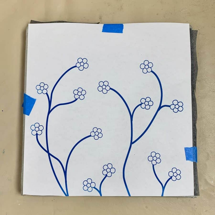 print of flowers taped to transfer paper and tile