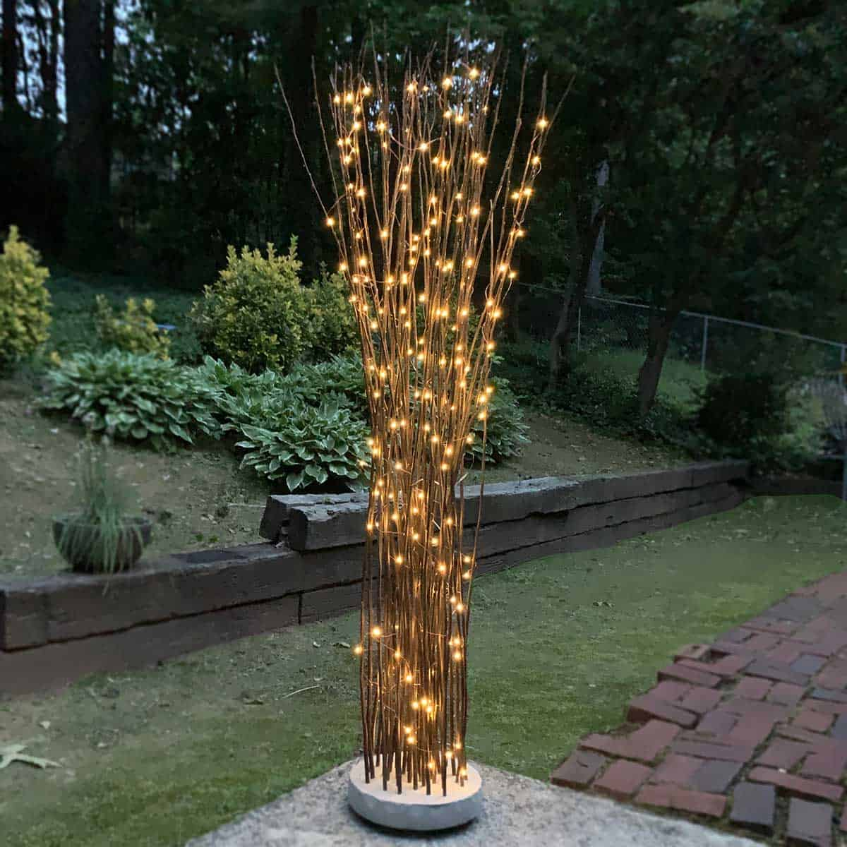 twigs in a floating cement stand on patio and lit