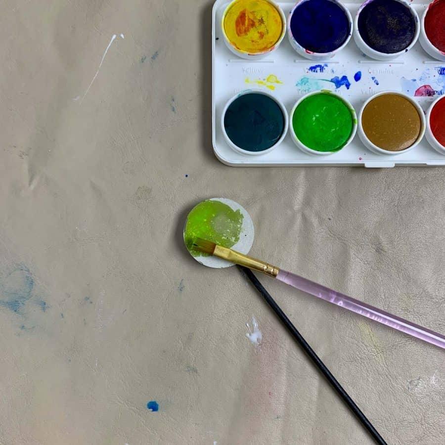 painting watercolor paint onto concrete garden label