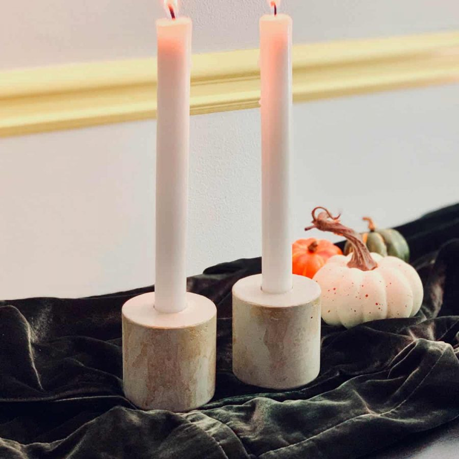 concrete candlestick holders with gold accents on green velvet
