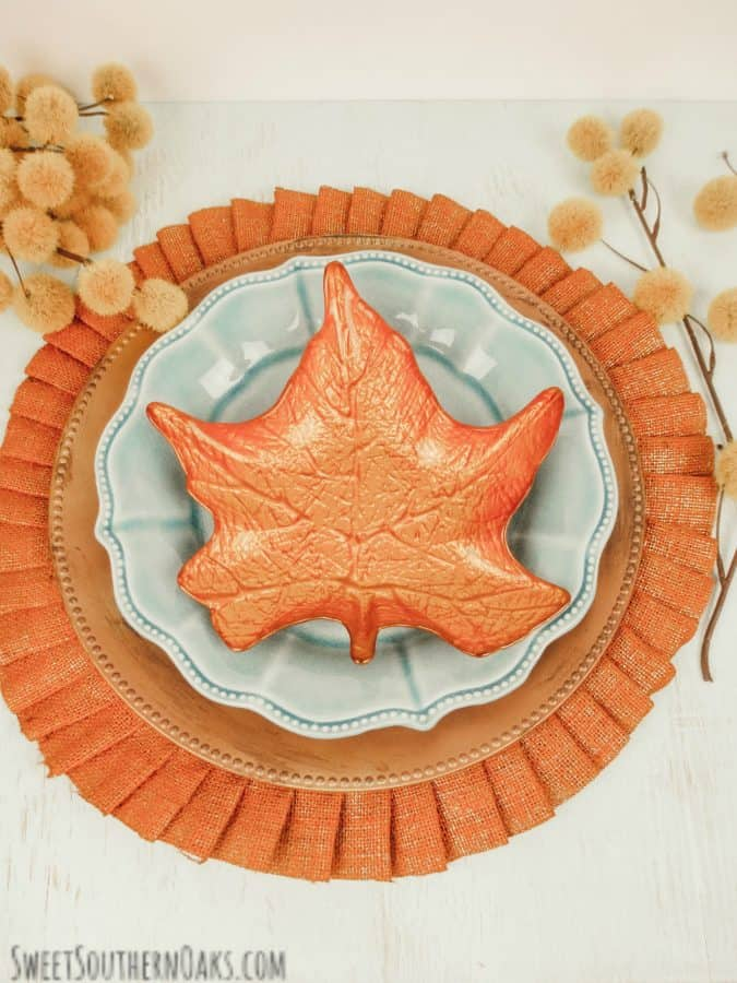 orange placemat with copper charger from dollar tree and orange metal leaf on top on a table