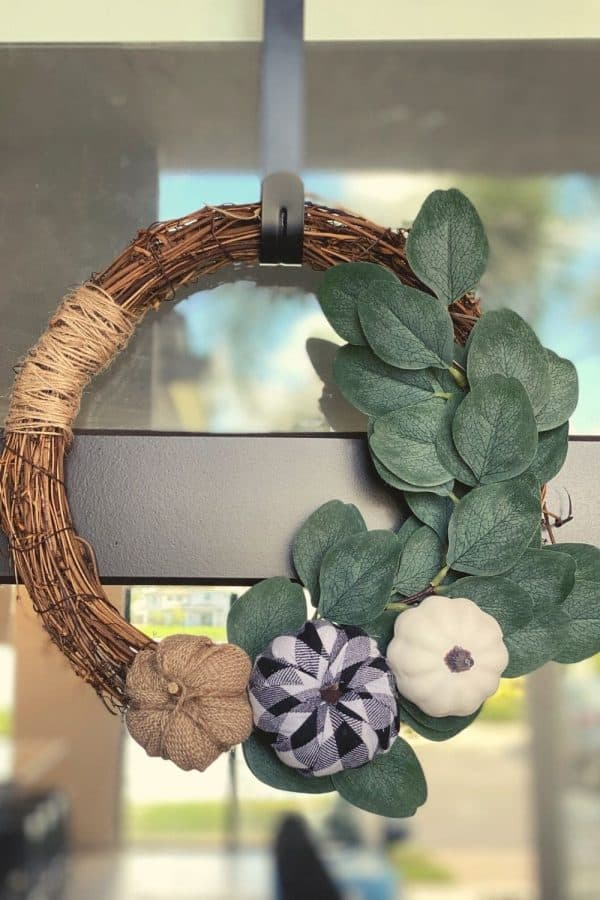Dollar Tree Fall Decor- a wreath hanging on a window made from twine, eucalyptus, and pumpkins