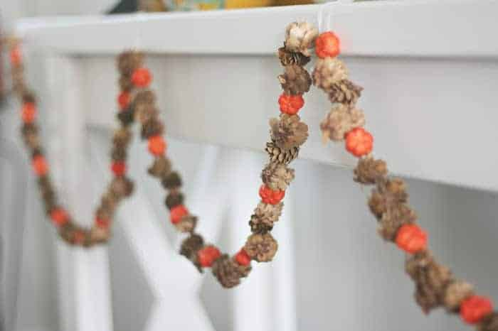 Dollar Tree Fall Decor- autumn garland diy, hanging from fireplace mantel. Made from mini pumpkins and pine cones.