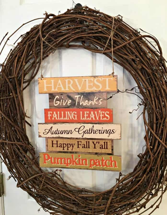 fall grape vine wreath with dollar tree added decor and a sign with thankful wording, on a door
