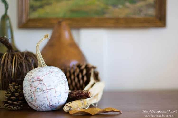 Dollar tree pumpkin craft on table with pine cones behind it. Pumpkin is wrapped in a map that's decoupaged