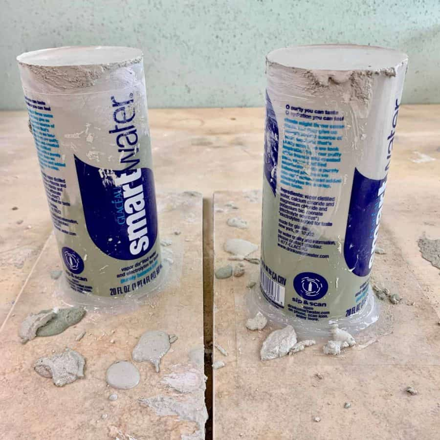 two DIY concrete pillar candle holder candles curing with marbled effect
