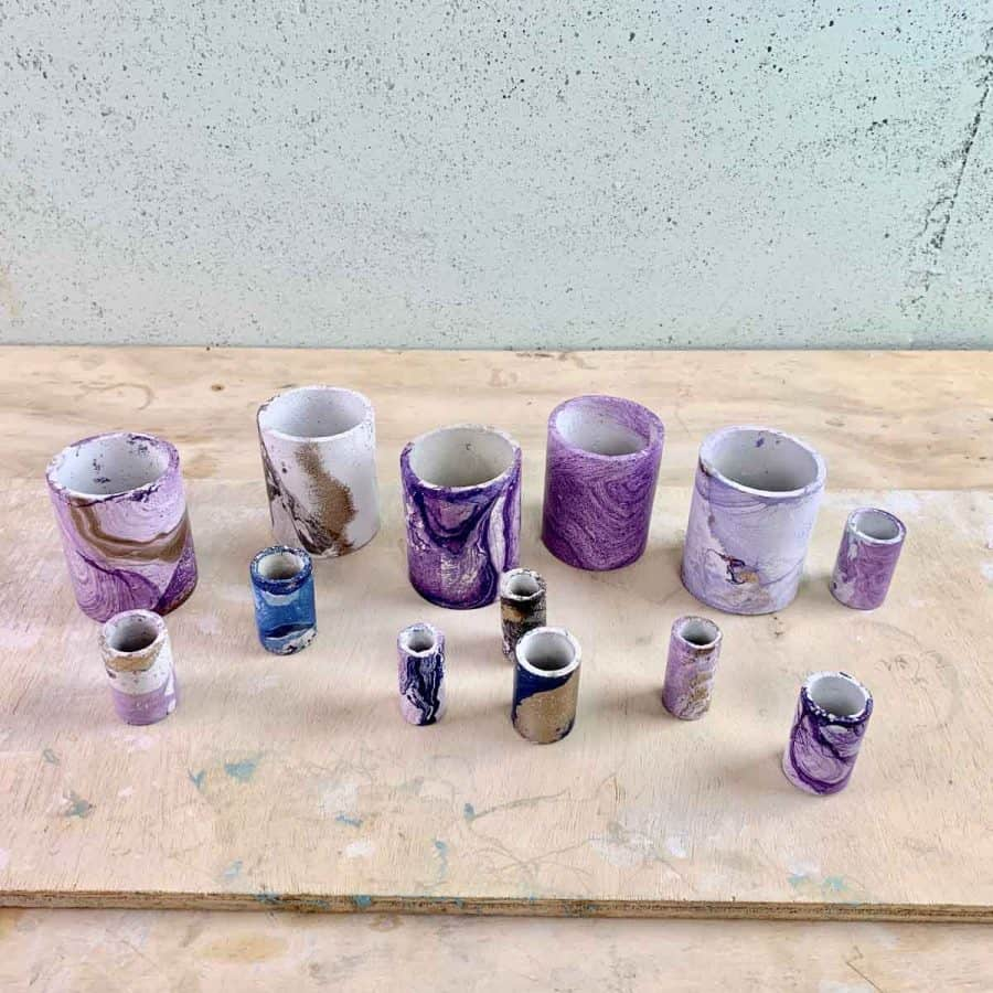 mabout a dozen planters that have been dipped and have many marbled colors