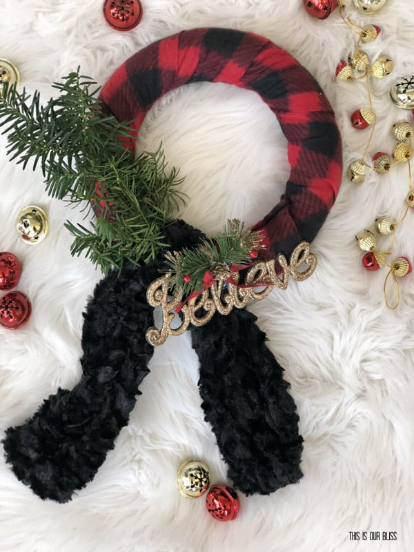 red plaid material wrapped around wreath base and black ruffle tie underneath