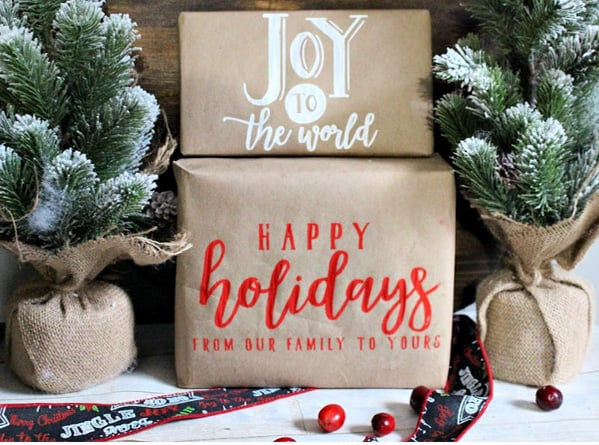 brown kraft paper wrapped gifts with chalk writing saying joy to the world and happy holidays