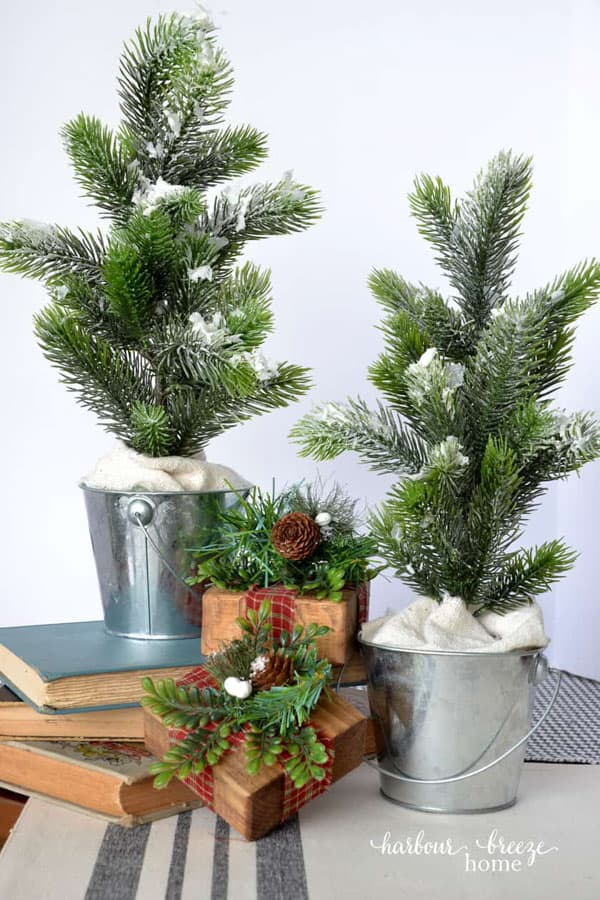 artificial christmas greenery inside galvanized pail, standing up to look like trees.