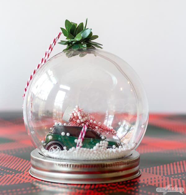 homemade snow globe ornament with tiny tree and mini cooper carrying it inside