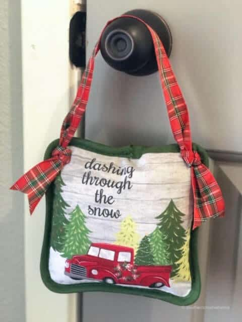 door knob decorated with pillow hanging on knob and design of red tuck says dashing through the snow