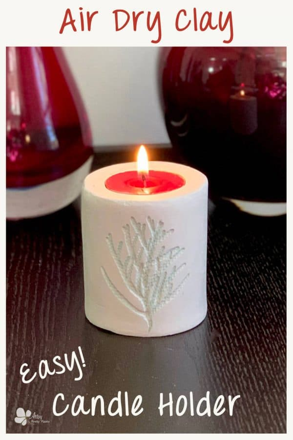 Clay Tealight Candle Holder on table with red vases, has cedar imprint