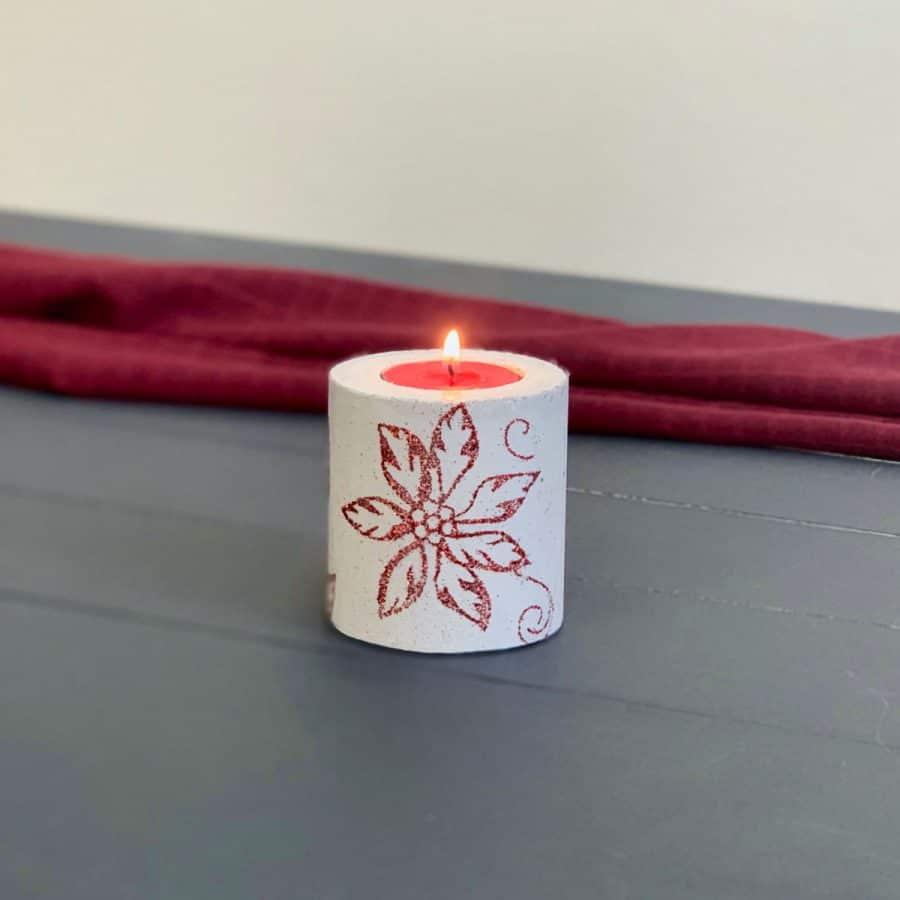 concrete candle on blue wood planks with red background. candle has poinsettia design