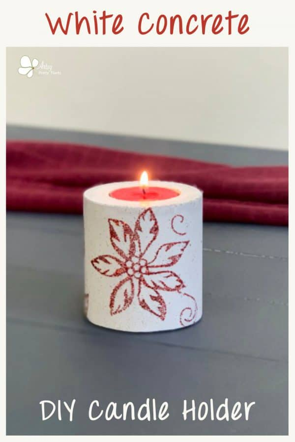 concrete candle on blue wood planks with red background. candle has poinsettia design. Made to be christmas gift