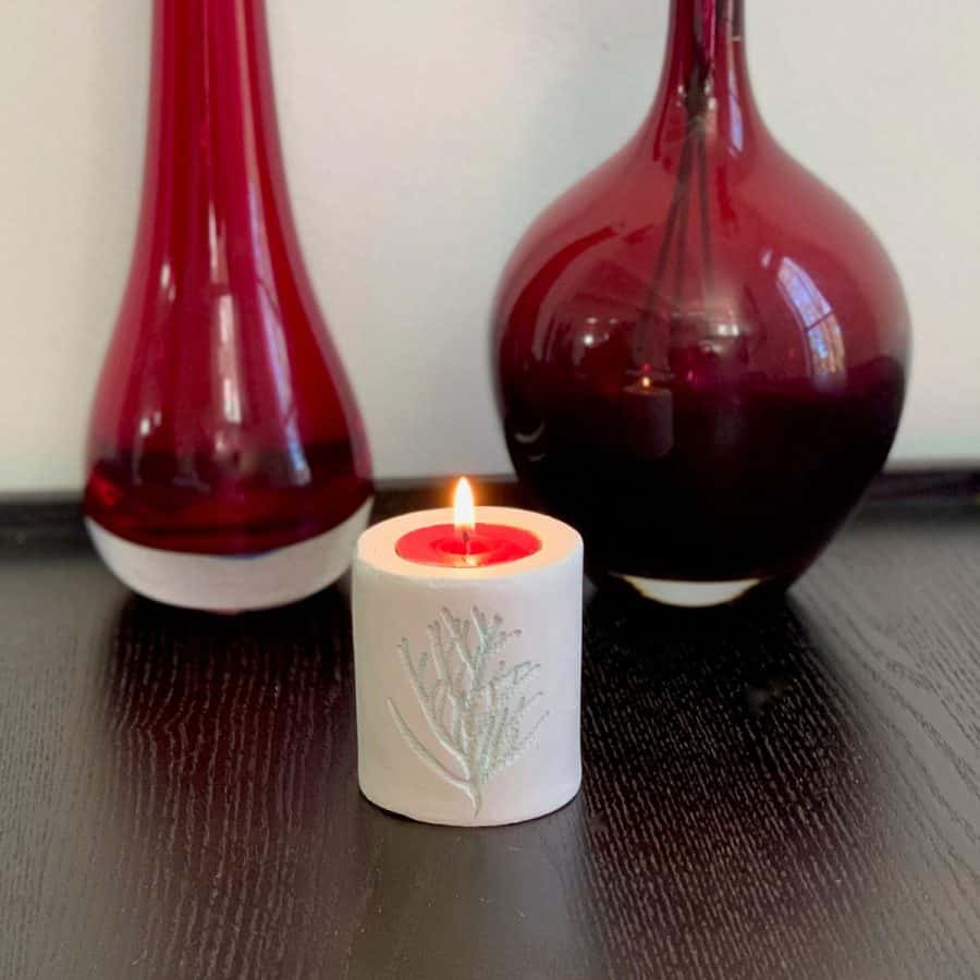 clay candle holder on table with red vases behind. candle has cedar leaf imprint
