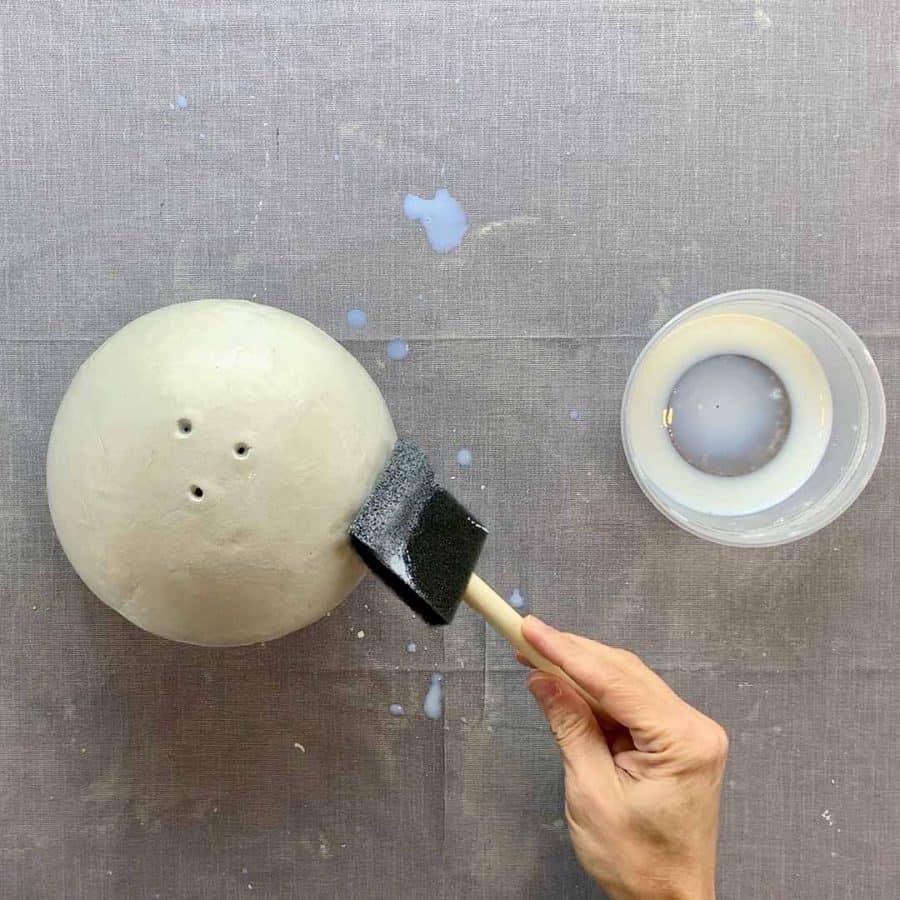 brush sealant onto diy clay balloon planter outside