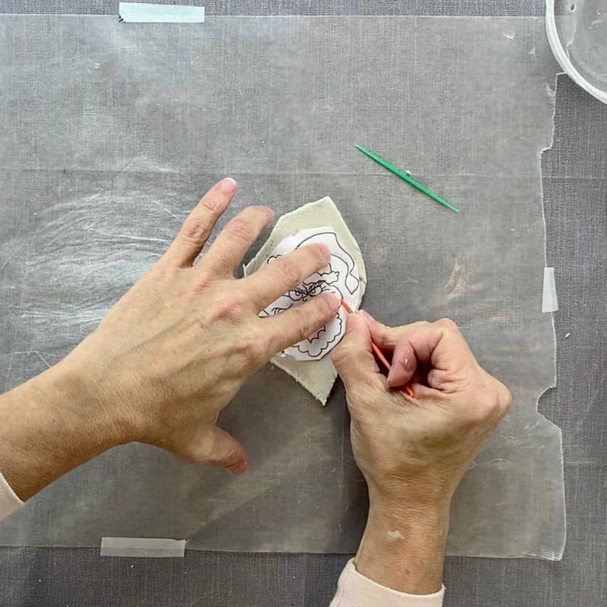 holding yarn needle to press grooves into paper transferring to clay