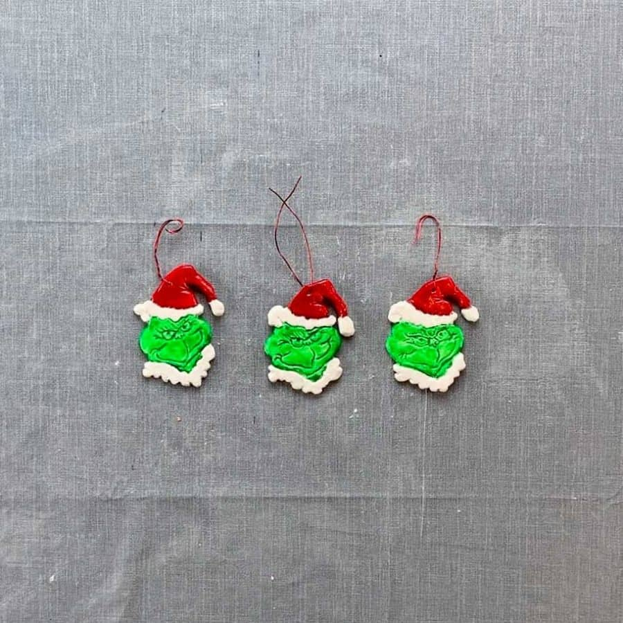 three diy grinch ornaments in a row with wire wrapped differently through hat