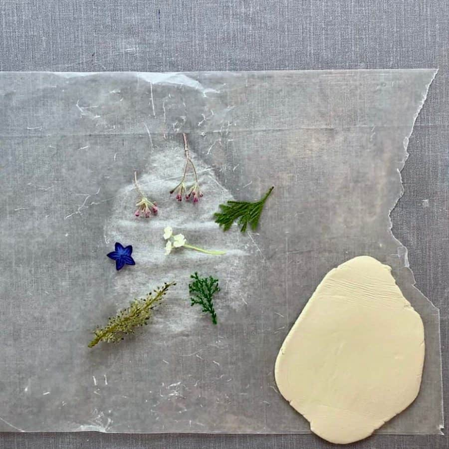 floral stems laid out on table next to rolled clay