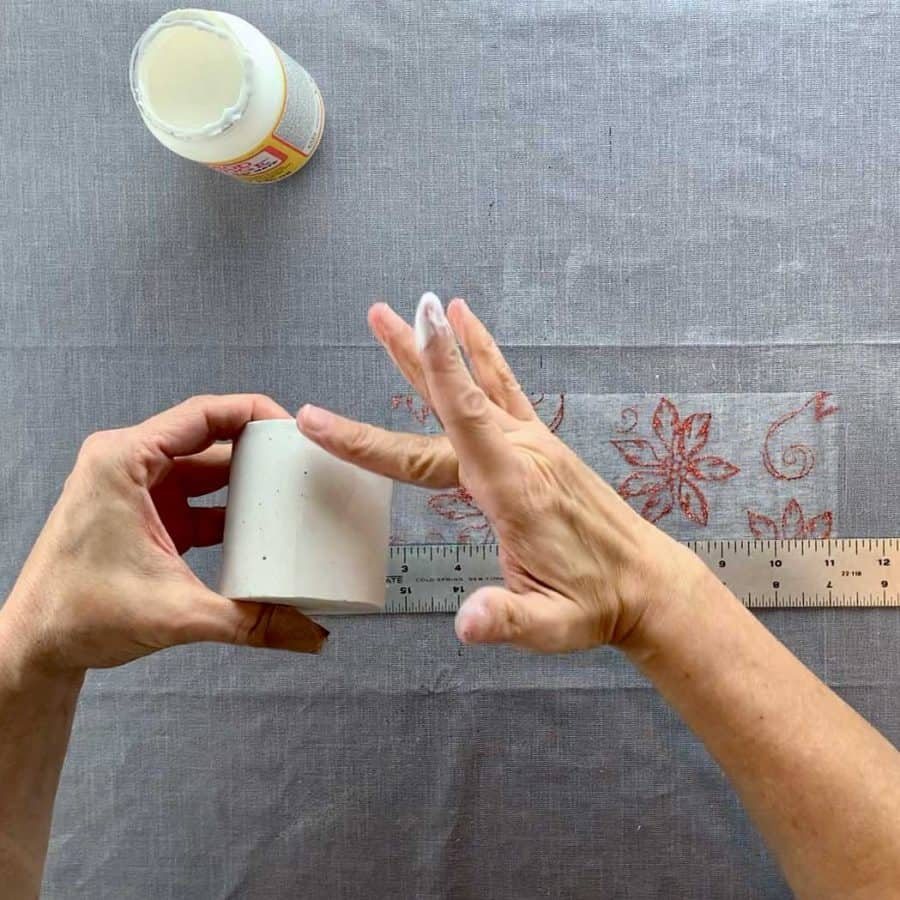 finger with glue applying to concrete candle