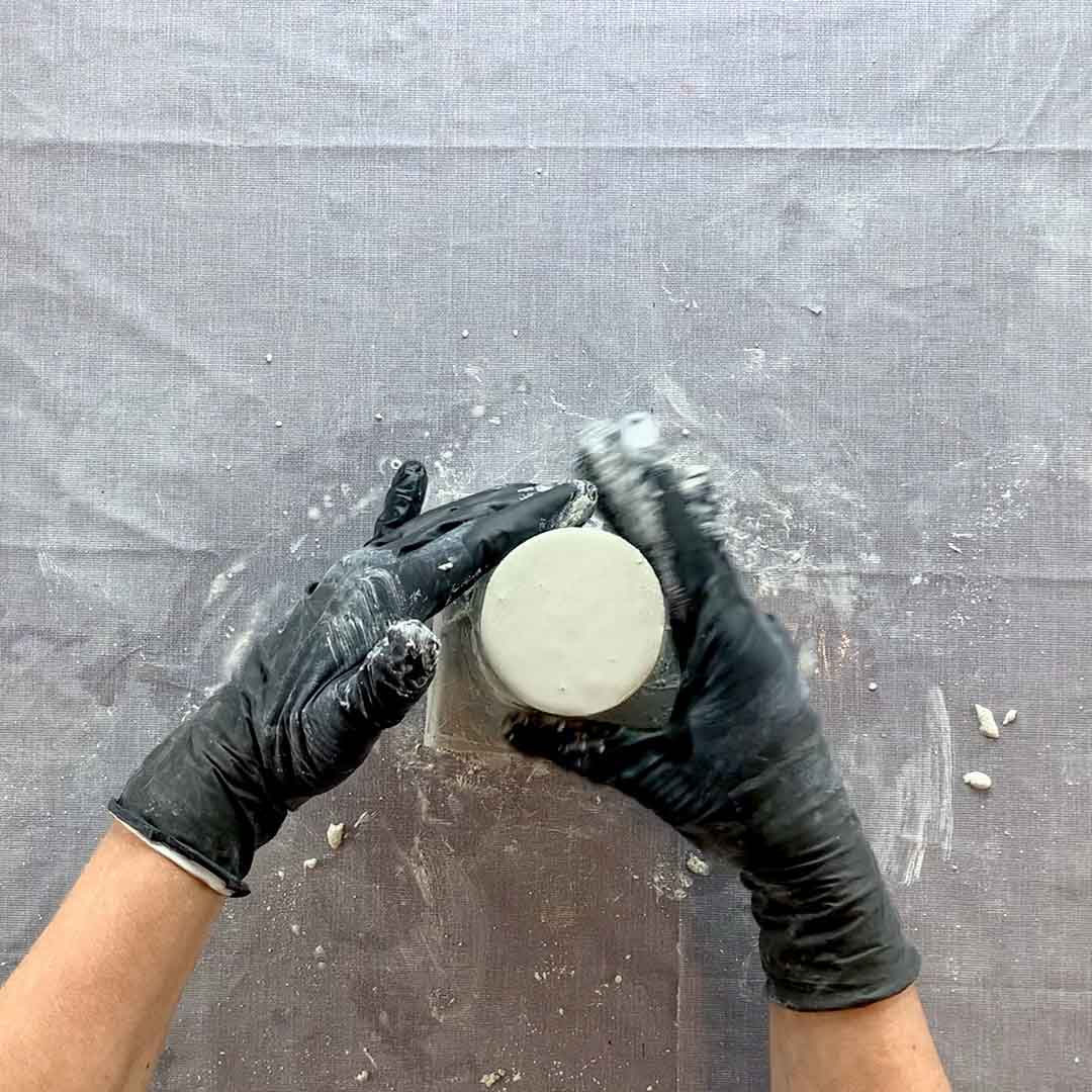 tapping concrete mold filled with white concrete
