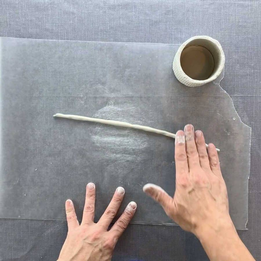 rolling out long skinny piece of clay