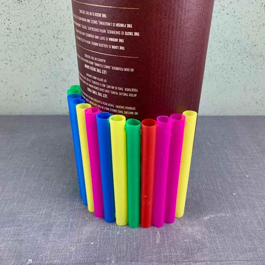 straws being glued around cardboard tube