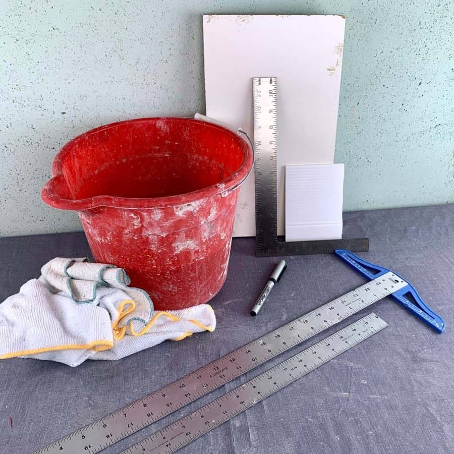 items for concrete crafts- bucket of water, melamine wood board, rulers and rags on table