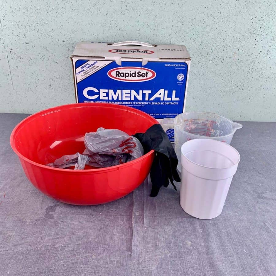 materials needed fore concrete crafts- bowl, cement, cups, gloves and bag on table