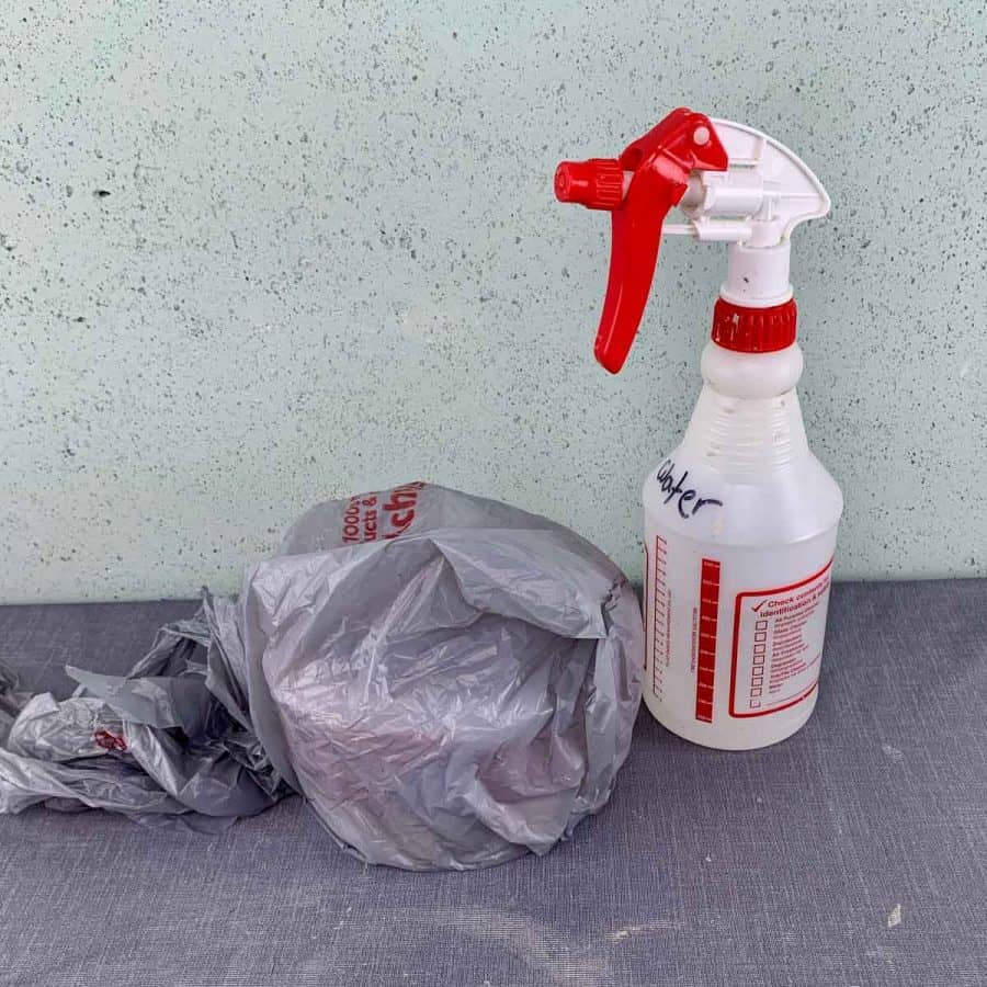 wet cure concrete inside of plastic bag with water bottle next to it