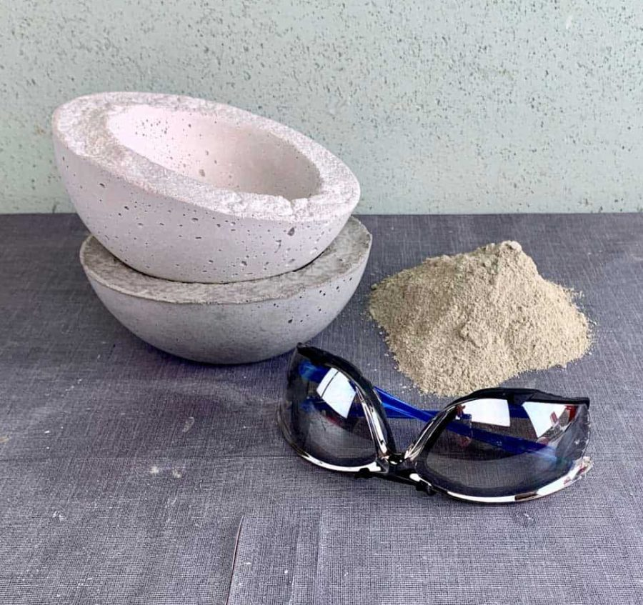 safety glasses, pile of dry cement mix and concrete bowls