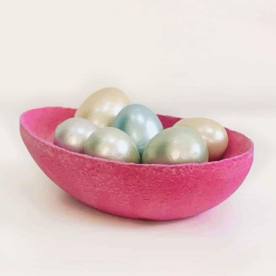 dark pink colored concrete bowl with pastel colored eggs inside